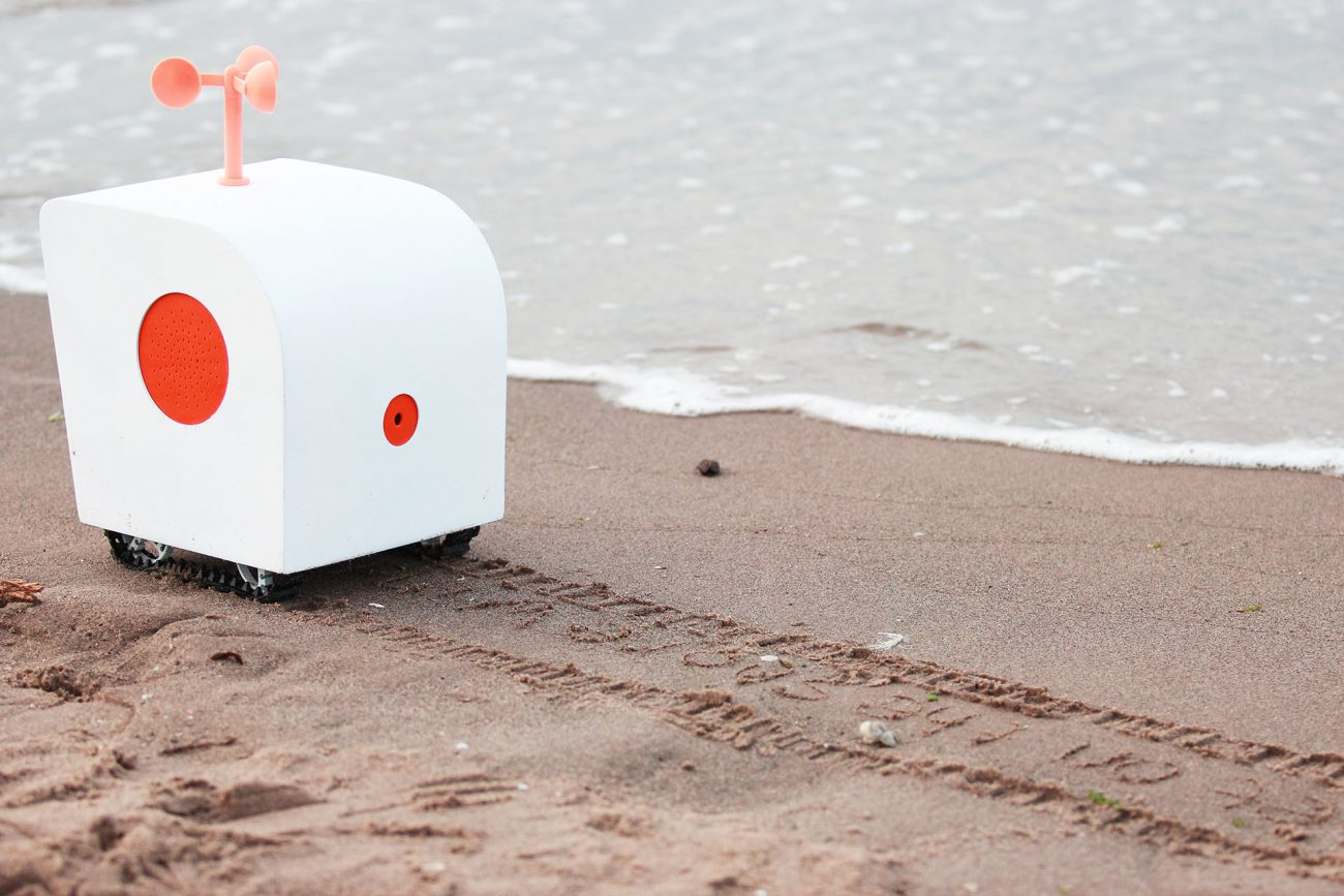Sensual robot the poet listens to the seagulls and writes poetry in the sand